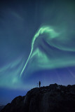 Person with a camera on rocky cliff under the aurora borealis