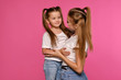 canvas print picture - Mom and daughter with a funny ponytails, dressed in white t-shirts and blue denim jeans are posing against a pink studio background. Close-up shot.