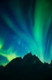 Aurora borealis dancing in night sky above mountain peaks and lake, Greenland