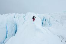 Person Exploring Walking Down Glacier Amongst Ice Crevasses