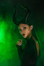 Concept Of Halloween And Fantasy Horror. Cosplay On Maleficent Demonic - Starring. Face Of Beautiful Woman From A Fairytale With Horns In Green Smoke. Beautiful Girl Dressed Up As Devil.