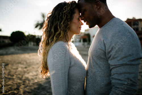 Couple embrace on beach at sunset - 294715432