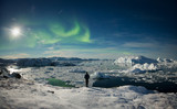 Person on shore of ice fjord overlooking icebergs and aurora borealis