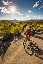 Woman Riding A Mountain Bike Outdoors On A Sunny Day