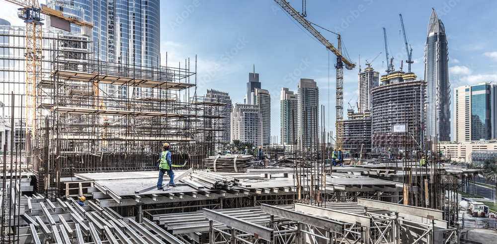 Fototapety, obrazy: Laborers working on modern constraction site works in Dubai. Fast urban development consept.