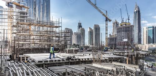 Foto auf Gartenposter Dubai Laborers working on modern constraction site works in Dubai. Fast urban development consept.