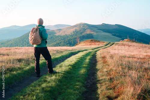 Foto auf Gartenposter Lachs Man with backpack on mountains road. Travel concept. Landscape photography