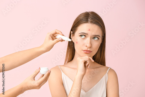 Portrait of young woman with acne problem and hands with remedy on color backgro Canvas Print