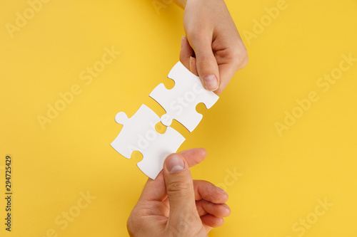 cropped view of woman and man matching pieces of white puzzle on yellow backgrou Canvas Print