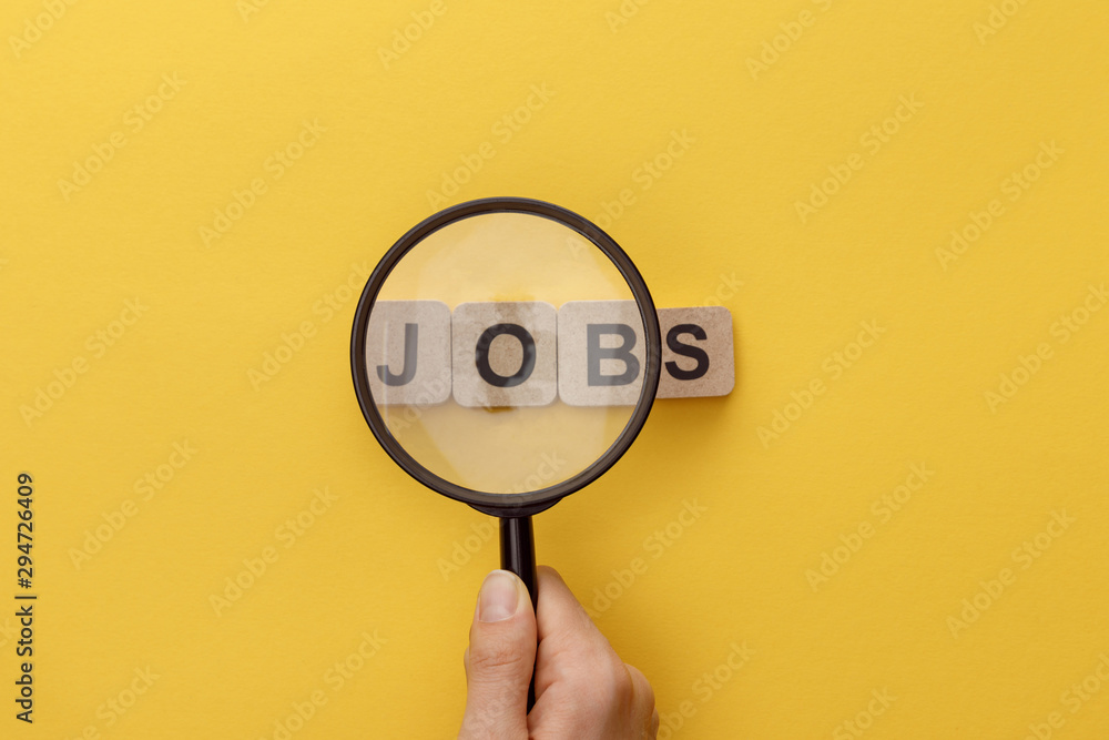 Fototapeta cropped view of woman holding magnifying glass under cardboard squares with jobs lettering on yellow background