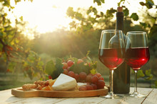 Glasses And Bottle Of Wine With Snacks On Wooden Table In Vineyard