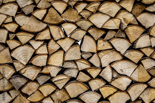 Wall of stacked wood logs as background. Pile of wood logs ready for winter