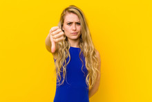 Young Blonde Woman Feeling Cross, Angry, Annoyed, Disappointed Or Displeased, Showing Thumbs Down With A Serious Look Against Yellow Wall