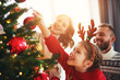 canvas print picture happy family mother, father and child daughter decorate Christmas tree  .
