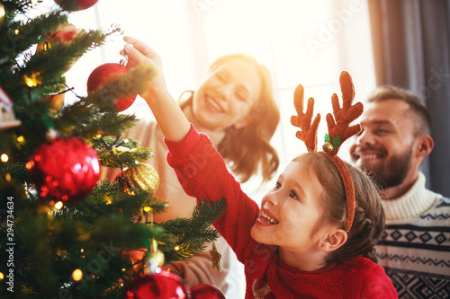 happy family mother, father and child daughter decorate Christmas tree  . - 294734634