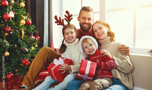 Deurstickers Wanddecoratie met eigen foto happy family with gifts near Christmas tree at home.