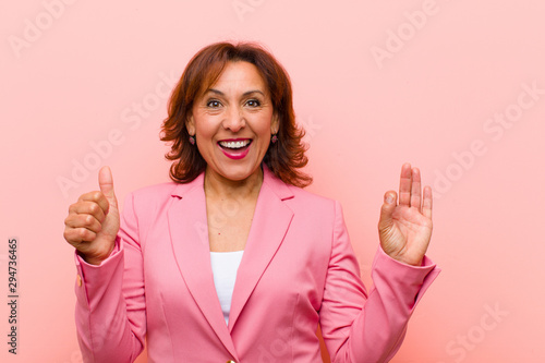 middle age woman feeling happy, amazed, satisfied and surprised, showing okay an Canvas-taulu