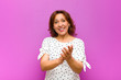 Leinwanddruck Bild - middle age woman feeling happy and successful, smiling and clapping hands, saying congratulations with an applause against purple wall