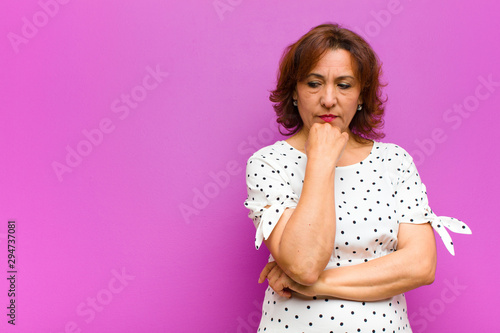 middle age woman feeling serious, thoughtful and concerned, staring sideways with hand pressed against chin against purple wall