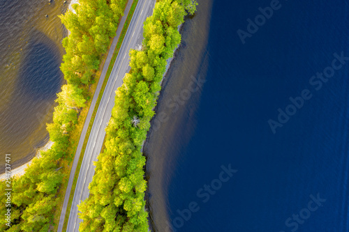 Arbre Aerial view of road between green summer forest and blue lake in Finland
