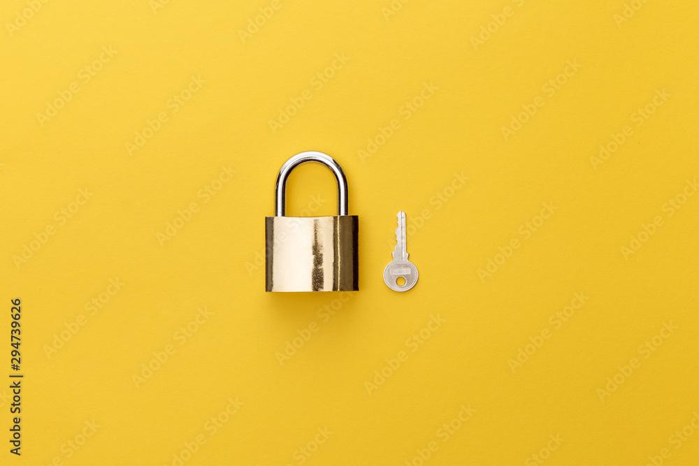 Fototapeta top view of padlock near key on yellow background