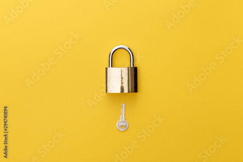 Fotomural  top view of padlock and key on yellow background