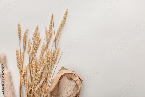 Fotografie, Tablou top view of wheat spikes, rolling pin and flour package isolated on white