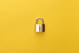 top view of metal padlock on yellow background