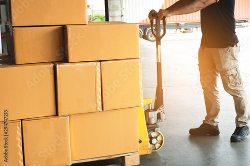 Warehouse worker working with hand pallet truck unloading goods pallet at wareho Canvas Print