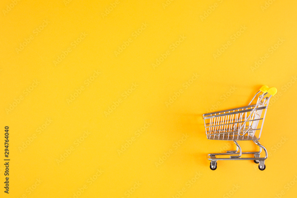 Fototapety, obrazy: Shopaholic. Buyer. Shopping concept. Close-up. Isolated shopping trolley on a yellow background. Copy space.