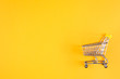 Leinwandbild Motiv Shopaholic. Buyer. Shopping concept. Close-up. Isolated shopping trolley on a yellow background. Copy space.