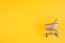 Shopaholic. Buyer. Shopping Concept. Close-up. Isolated Shopping Trolley On A Yellow Background. Copy Space.