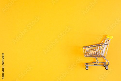 Obraz Shopaholic. Buyer. Shopping concept. Close-up. Isolated shopping trolley on a yellow background. Copy space. - fototapety do salonu
