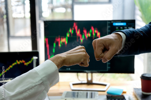 group businessman fist bump hand at the office table between computer laptop Canvas