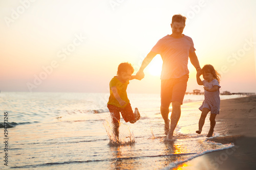 happy  family father and two children playing on the beach  run at the sunset time Canvas Print