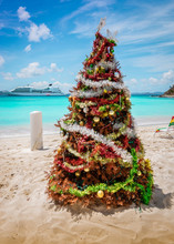 Decorated Christmas Tree On White Sand Caribbean Beach, Jost Van Dyke, British Virgin Islands. Cruise Ship In The Background.