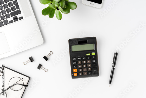 Office desktop with calculator and accessories on white background. Financial concept. Top view
