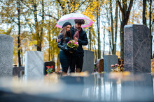 Couple Mourning A Deceased Loved One On Cemetery In Fall