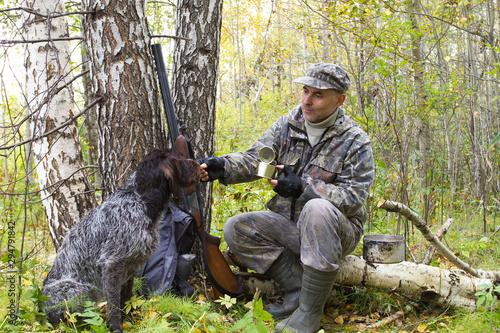 hunter feeds the gundog at a halt Fototapet