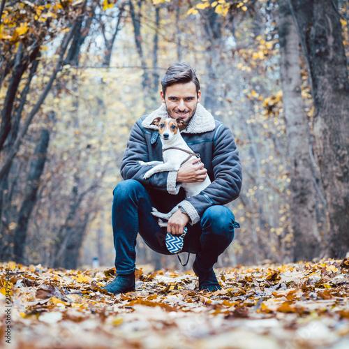 Fotografía  Young man walking his dog having a stroll in the autumn park