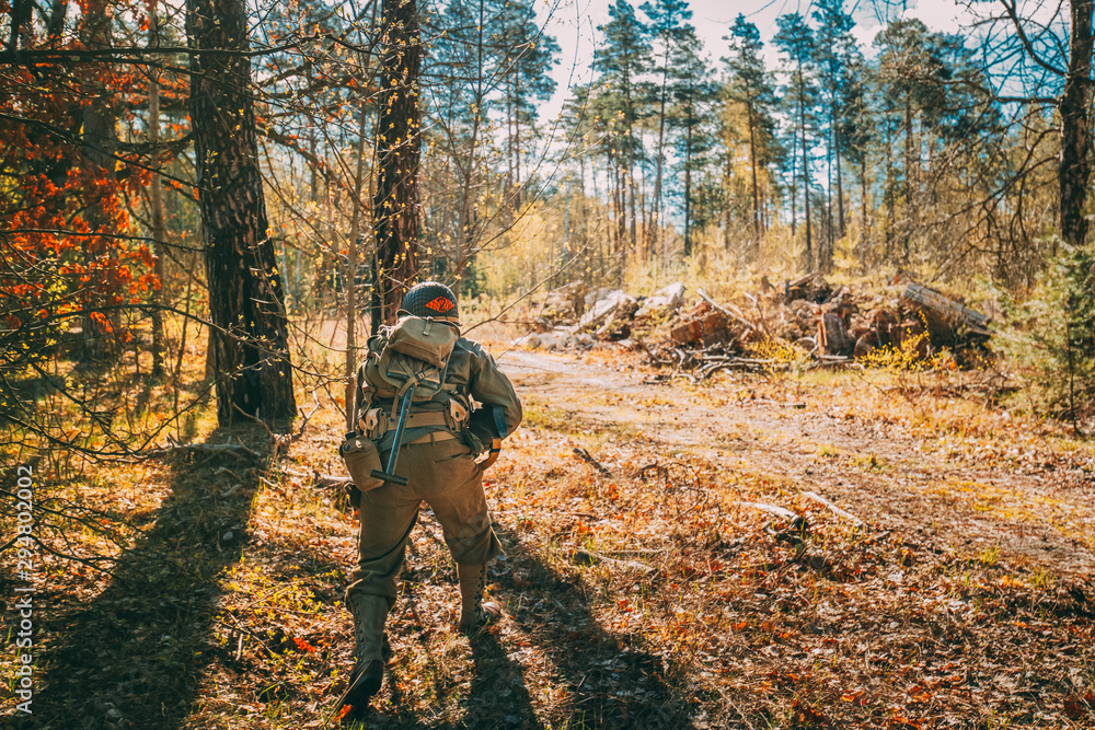 Fototapeta Re-enactor Dressed As Soldier Of United States Of America Infantry Of World War II Hidden Running With Sub-machine Gun In Forest At Historical Reenactment