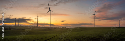 Obraz windmills on a field in Germany during a beautiful multicolored sunrise - fototapety do salonu