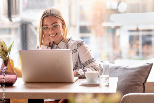 Portrait of young woman using laptop at cafe, she is working on laptop computer at a coffee shop. - 294805496