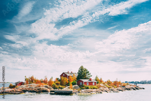 Suomi Or Finland. Beautiful Red Finnish Wooden Log Cabin House On Rocky Island Coast In Summer Sunny Evening. Lake Or River Landscape. Tiny Rocky Island Near Helsinki, Finland