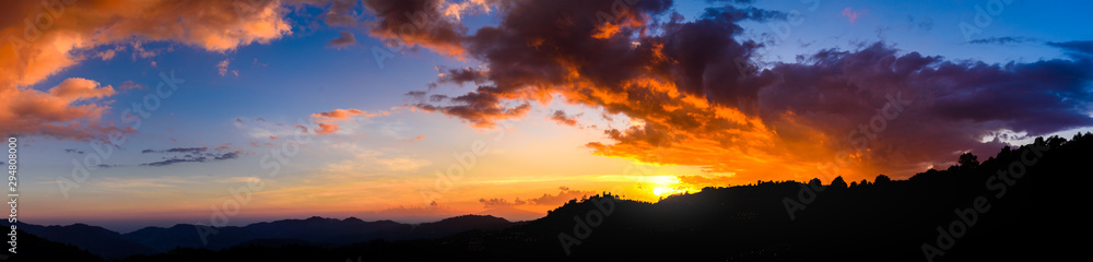 Panoramic landscape of Mountains at sunset with clouds