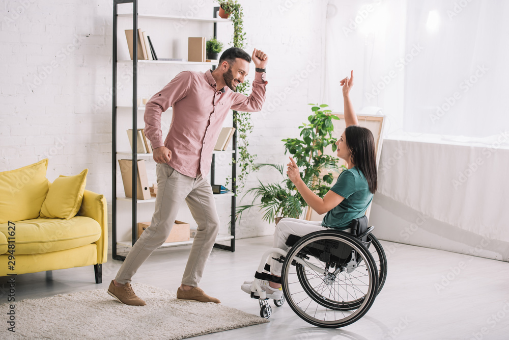 Fototapety, obrazy: happy disabled woman on wheelchair dancing with cheerful boyfriend at home