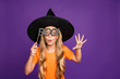 canvas print picture - Boo. Photo of little witch lady play enchantress role halloween party holding paper stick scary look wear orange t-shirt wizard hat isolated purple color background