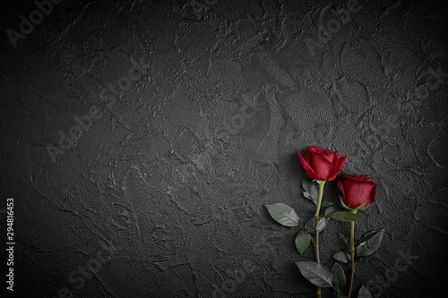 Fotomural  Red roses are placed on a black textured background