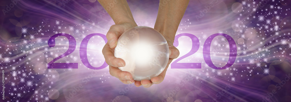 Fototapeta Experience a Crystal Ball Reading - What does 2020 hold for you - female hands holding a large clear crystal ball between 20 and 20 making 2020 against a wide purple sparkling flowing background