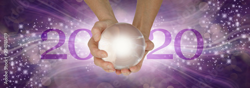 Obraz Experience a Crystal Ball Reading - What does 2020 hold for you - female hands holding a large clear crystal ball between 20 and 20 making 2020 against a wide purple sparkling flowing background  - fototapety do salonu